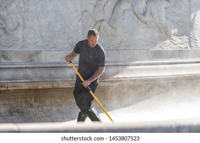 London, UK - June 22, 2018: Buckingham Palace water fountain with man worker spraying cleaning stone monument on street in sunny summer morning day