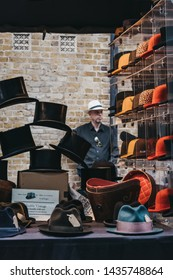 London, UK - June 22, 2019: Man behind hats on sale at a stall inside Spitalfields Market, one of the finest surviving Victorian Market Halls in London with stalls offering fashion, antiques and food.
