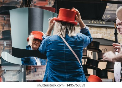 London, UK - June 22, 2019: Woman trying on hats at stall inside Spitalfields Market, one of the finest surviving Victorian Market Halls in London with stalls offering fashion, antiques and food.