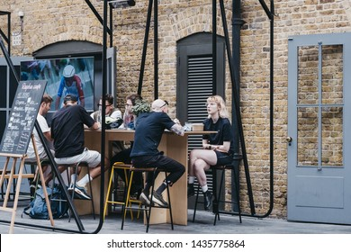 London, UK - June 22, 2019: People enjoying food and drinks at Rapha cafe inside Spitalfields Market, one of the finest Market Halls in London with stalls offering fashion, antiques and food.