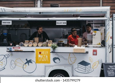 London, UK - June 22, 2019: Staff at Lovely Pasta food truck inside Spitalfields Market, one of the finest Victorian Market Halls in London with stalls offering fashion, antiques and food.