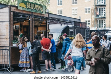London, UK - June 22, 2019: People walking past queue at Beijummy stall inside Spitalfields Market, one of the finest Market Halls in London with stalls offering fashion, antiques and food.