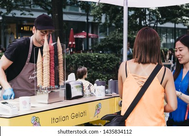 London, UK - June 22, 2019: Women buying fresh Italian Gelato from a cart inside Spitalfields Market, one of the finest Victorian Markets in London with stalls offering fashion, antiques and food.