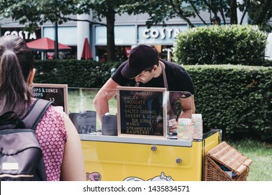 London, UK - June 22, 2019: Woman buying fresh Italian Gelato from a cart inside Spitalfields Market, one of the finest Victorian Markets in London with stalls offering fashion, antiques and food.