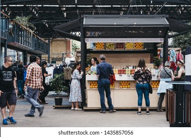 London, UK - June 22, 2019: People buying fresh juice from Pink Grapefruit greengrocer at Spitalfields Market, one of the finest Market Halls in London with stalls offering fashion, antiques and food.