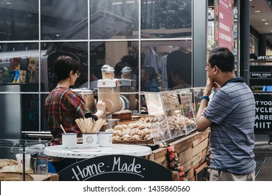 London, UK - June 22, 2019: Man ordering coffee and sweets at a stand inside Spitalfields Market, one of the finest Victorian Market Halls in London with stalls offering fashion, antiques and food.