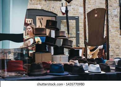 London, UK - June 22, 2019:People looking at hats at stall inside Spitalfields Market, one of the finest surviving Victorian Market Halls in London with stalls offering fashion, antiques and food.
