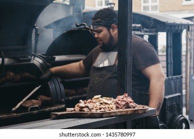 London, UK - June 22,2019:Meat samples at a Smokoloco stall, staff cooking on the background inside Spitalfields Market, one of the finest Market Halls in London with stalls offering fashion and food.