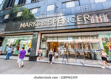 London, UK - June 24, 2018: Marks & Spencer store shop with people walking exiting on sidewalk in Soho with large sign exterior entrance