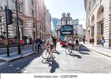 London, UK - June 26, 2018: Many people men pedestrians on bicycles riding waiting for traffic light on bikes street road in center of downtown financial district city, old architecture, sunny summer
