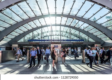 London, UK - June 26, 2018: People crowd commuters in front of outside Underground tube metro entrance during morning commute in Canary Wharf with modern architecture