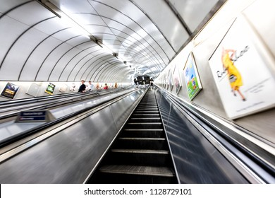 London, UK - June 26, 2018: People riding escalator up and down standing in Underground tube metro in Pimlico district area of city through tunnel