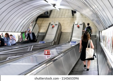 London, UK - June 26, 2018: Pimlico tube station, underground escalator in city with people, woman walking up and down in covered tunnel