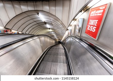 London, UK - June 26, 2018: Pimlico tube station, underground escalator in city wide angle with people, woman walking riding down in covered tunnel