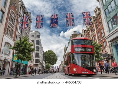 LONDON, UK - JUNE 28, 2016:  A bus passes shoppers and British flags on busy Oxford Street