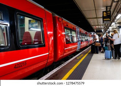 London, UK - June 28, 2018: Gatwick Express metro with red subway train in London Victoria Station, people waiting on platform station