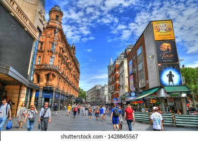 LONDON, UK, JUNE 3: colorful HDR image of tourists at the famous Leicester Square, one of the most popular sites in London with its famous sings on dramatic blue sky. London, UK, June 3, 2019
