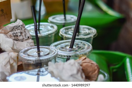 London, UK, June 30, 2019: Plastic single use glasses with paper straws on the bin at the food market