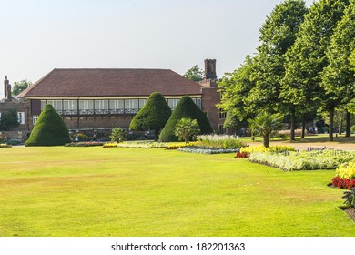 LONDON, UK - JUNE 4, 2013: View of beautiful garden in Hampton Court Palace in London. Hampton Court was originally built for Cardinal Thomas Wolsey, a favorite of King Henry VIII, circa 1514.