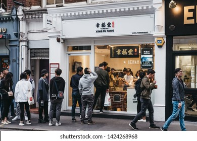 London, UK - June 5, 2019: People queuing for take away from from Xing Fu Tang Taiwan shop in Chinatown, London. Chinatown is home to an East Asian community and is famous for its eateries and events.