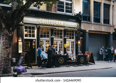 London, UK - June 5, 2019: People drinking outside the College Arms pub, a contemporary pub in Bloomsbury area in West End of London famed for fashionable residential area and numerous pubs and cafes.
