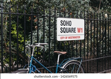 London, UK - June 5, 2019: Street name sign on a fence by parked bicycle in Soho Square, City of Westminster, a borough that occupies much of the central area of London including most of the West End.