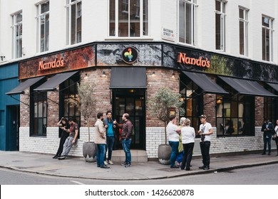 London, UK - June 5, 2019: People standing outside Nandos restaurant in Soho, London, logo coloured with rainbow colours. Soho is an area of London famous for LGBTQ+ bars, restaurants and clubs.
