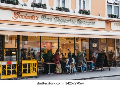 London, UK - June 5, 2019: People sitting at the outdoor tables of Govinda's Pure Vegetarian Restaurant, one of London's oldest vegetarian eateries.