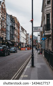London, UK - June 5, 2019: Street name sign on Greek Street in Soho, an area of London famous for LGBTQ+ bars, restaurants and clubs.