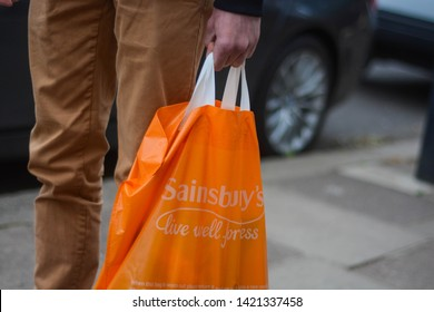 London, UK, June 6, 2019: Sainsbury's shopping bag  in hand of a young male