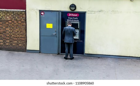 LONDON, UK - JUNE 9, 2015: Man using his credit card in an atm for cash withdrawal