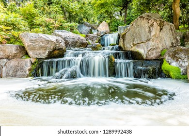 London, UK Kyoto Japanese Garden in Holland Park with green summer peaceful zen lake pond waterfall and long exposure smooth water