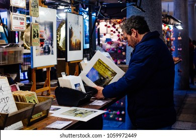 London / UK - March 10, 2018: tourist is looking for Banksy photos in souvenir shop in Covent Garden's Market, London, UK. Covent Garden is popular shopping and tourist site in London