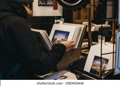 London, UK - March 10, 2018: Man looking through Banksy posters on sale at Covent Garden Market, one of the oldest markets in London famous for its unique handmade crafts.