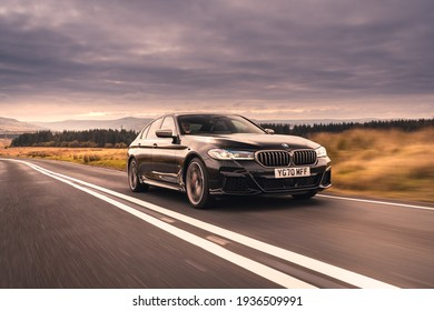London, UK- March 10, 2021: A black BMW M550i xDrive sedan is driven on road