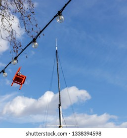 LONDON, UK - MARCH 11 : Red chair hanging from an electricty cable on the Embankment in London on March 11, 2019