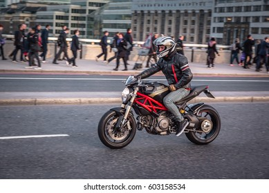 London , UK - March 13th 2017. London rush hour. Commuters and office workers crossing London Bridge during their rush hour commute.Panning type photo of motorcycle  speeding through traffic.