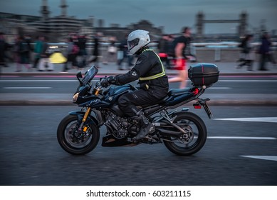 London , UK  March 13th 2017. London rush hour traffic. Commuters and office workers crossing London Bridge during their rush hour commute. Panning type of photography of a motorcycle