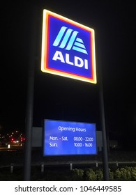 London, UK: March 14, 2018: Illuminated Sign outside an Aldi store with opening hours. Aldi is the common brand of two discount supermarket chains with over 10,000 stores in 20 countries.