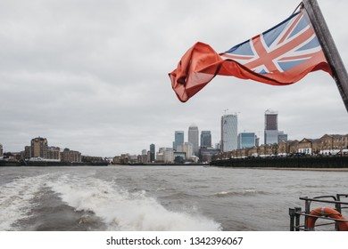 London, UK - March 16, 2019: British Naval Flag on Thames Clippers boat on River Thames, Canary Wharf on the background. Canary Wharf is a busy financial area of London, UK.