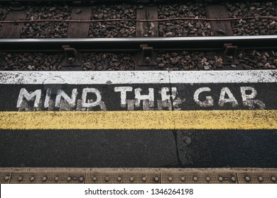 London, UK - March 16, 2019: Mind the gap sign an outdoor platform of Golders Green station. London Underground is the oldest underground railway in the world.