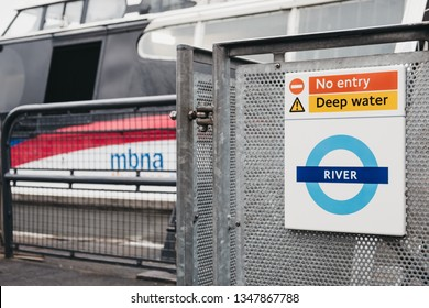 London, UK - March 16, 2019: Close up of a Transport for London River sign, MBNA Thames Clippers boat on the background. The Clippers are the fastest and most frequent fleet on the River Thames.