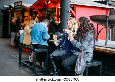 LONDON, UK - MARCH 18, 2017: Young women eating and taking a photo of dessert in hand at Street Food Market in Shoreditch