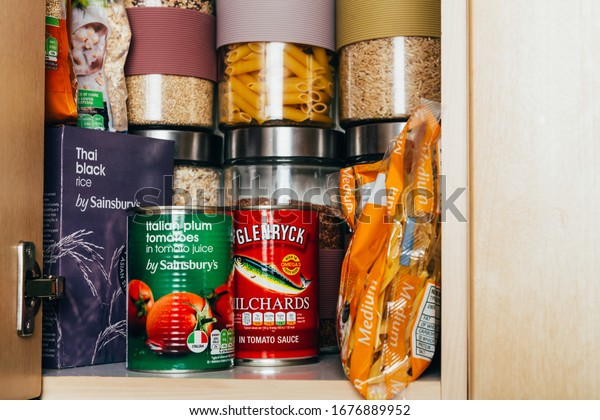 London, UK: March 18, 2020: Cupboard shelves fool of food provision, such as pasta, rice, porridge, canned tuna, beans and more. Panic buying to survive Coronavirus COVID 19 pandemic during lock down.
