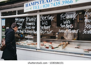 London, UK - March 2, 2019: People by fishmonger stall at Hampstead Community Centre market in Hampstead, an affluent residential area of London favoured by artists and media figures.