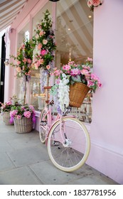London, UK / March 2, 2020 - Portrait View of a Pink Bicycle Surrounded by Artificial Flowers Outside a Pink Cake Shop from London, UK