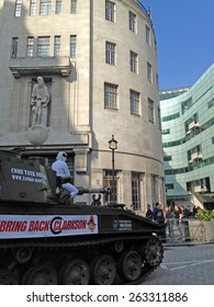 LONDON, UK - March 20, 2015:  The Stig on top of a tank outside BBC Broadcasting House delivering a petition in support of Top Gear presenter Jeremy Clarkson.