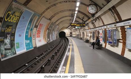 London, UK, March, 20, 2020: Underground platform with lonely woman waiting train on empty subway station at coronavirus lockdown