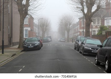 LONDON, UK - MARCH, 2017: Fog in early morning on residential sidestreet in London. Empty street and parked cars.