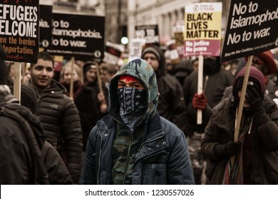 London, UK - March 2018: Alleged Antifa protester at the 'Stand Up To Racism' rally mingle amongst protesters after being dispersed by police after flairs were let off in Piccadilly Circus.